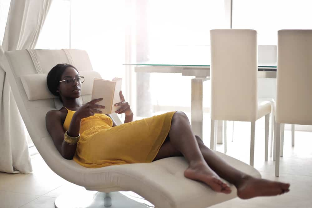 A woman reading a book on a white tufted recliner chair.