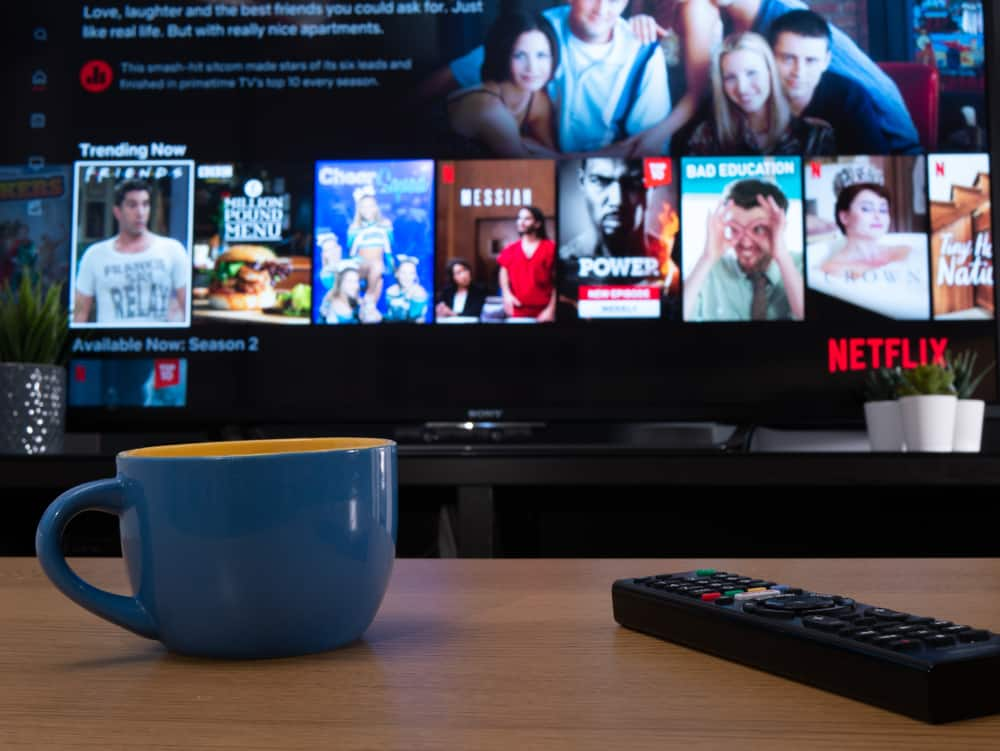 A close look at a cup of coffee on a wooden coffee table across from the TV that features Netflix.
