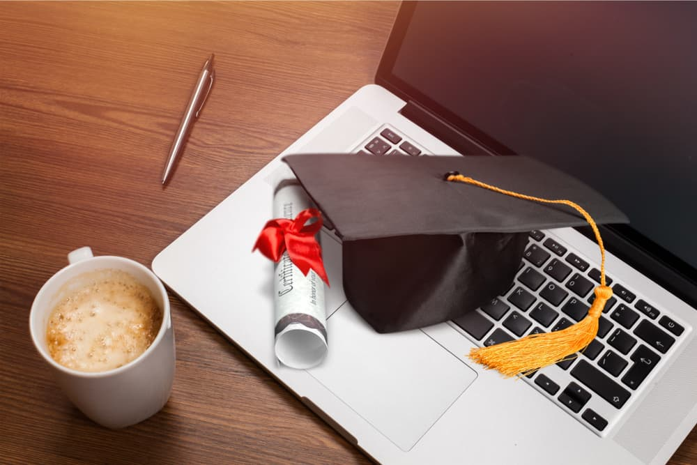 A cup of coffee along with a laptop topped with a graduation cap and diploma.