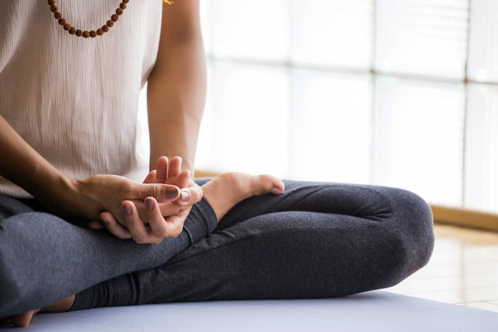 Woman practicing meditation indoors.