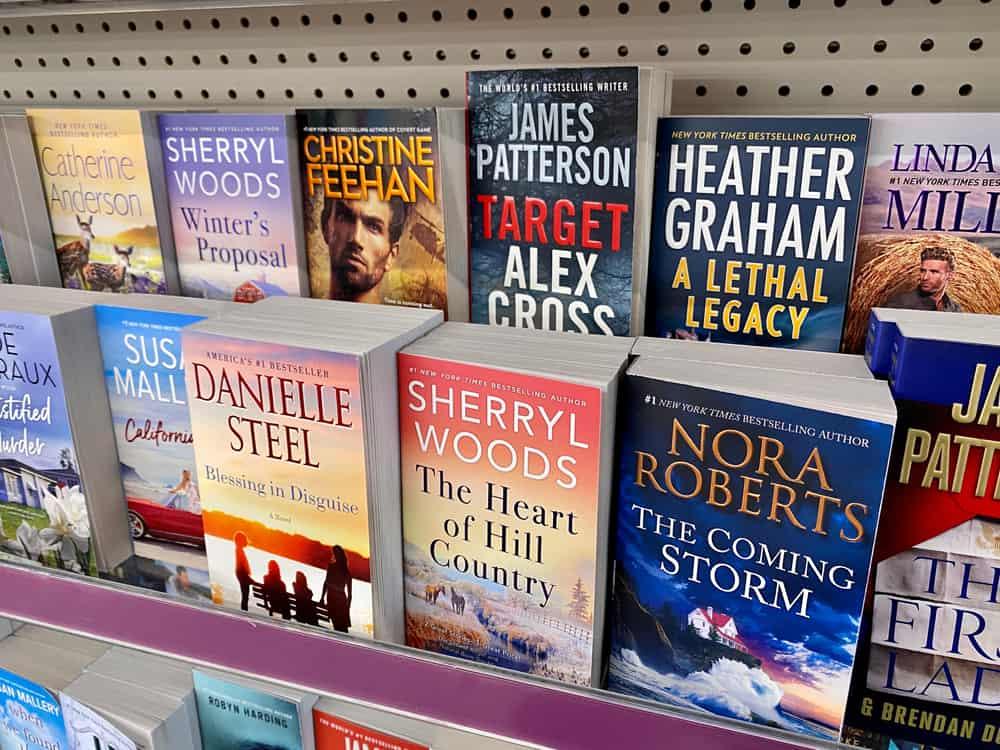 Variety of fiction books on a shelf inside a store.