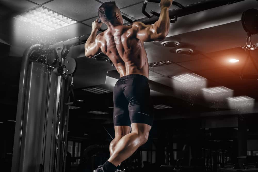 This is a man doing pull-ups at the gym.