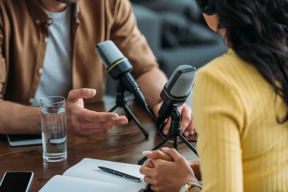 Two radio hosts recording podcast in broadcasting studio.