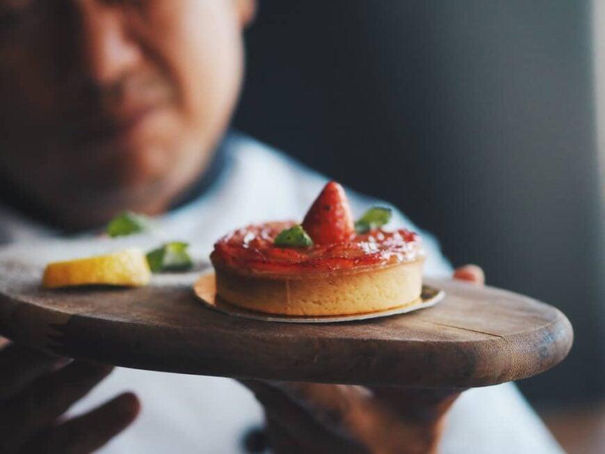 Master chef holding a strawberry tart.