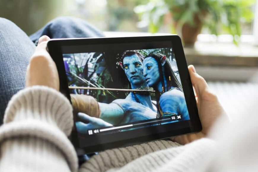 A person watching the movie Avatar on a tablet.