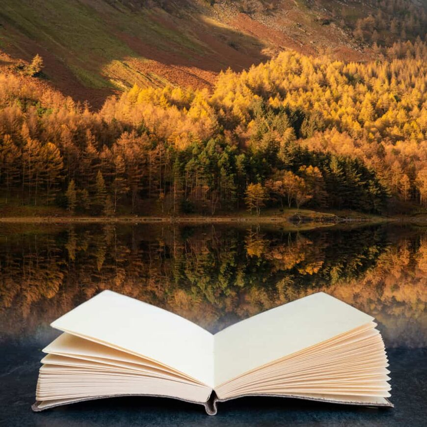 This is an open empty book across a lake to a pine forest with autumn colors.